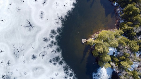 Aerial photo of the shore and a lake partially frozen over during Vermont Spring