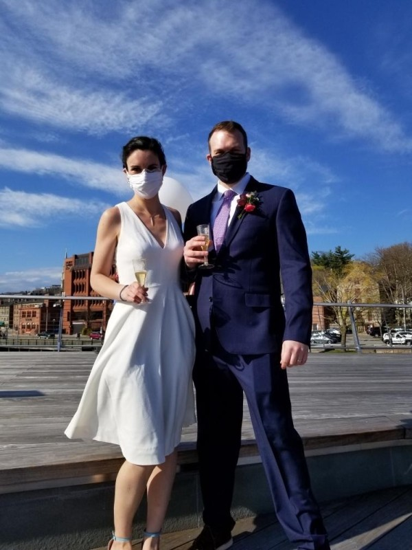 Newly wed couple wearing wedding attire and face masks holding up glasses of champagne